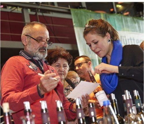 Man sieht Besucher, die sich bei der Weinprobe beraten lassen