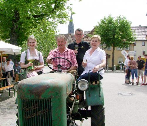 Man sieht Jürgen Stilling, Vorsitzender des Weinbauvereins Markelsheim, seinen Vorgänger Thomas Lehr (am Steuer), rechts im Bild Bad Mergentheims Bürgermeisterin Claudia Kemmer und links die frühere Markelsheimer Weinkönigin Doreen Hartmann.