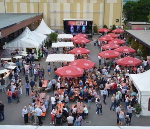 Man sieht den Innenhof der Genossenschaftskellerei Heilbronn, mit zahlreichen Probierständen, Sonnenschirmen, einem Pavillon und zahlreichen Besuchern des Sommerfests, Im Hintergrund sieht man eine kleine Bühne.