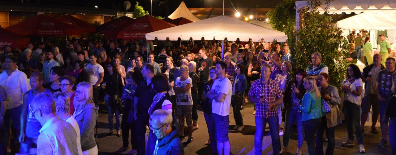 Man sieht zahlreiche Besucher in nächtlicher Kulisse beim Sommerfest der Genossenschaftskellerei Heilbronn-Erlenbach-Weinsberg