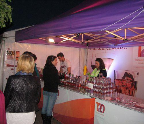 Man sieht mehrere Gäste beim Kelterfest am Stand von Trollinger 2.0, wie sie der Herstellung ihrer bestellten Cocktails zusehen.