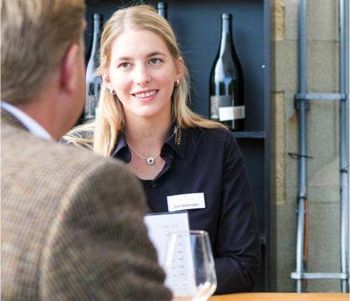 """Am Stand der Jungwinzervereinigung """"Vinitiative"""" bei """"Wein auf der Insel 2017"""", man sieht ein Mitglied der Vinitiative im Gespräch mit einem Gast am Stand."""