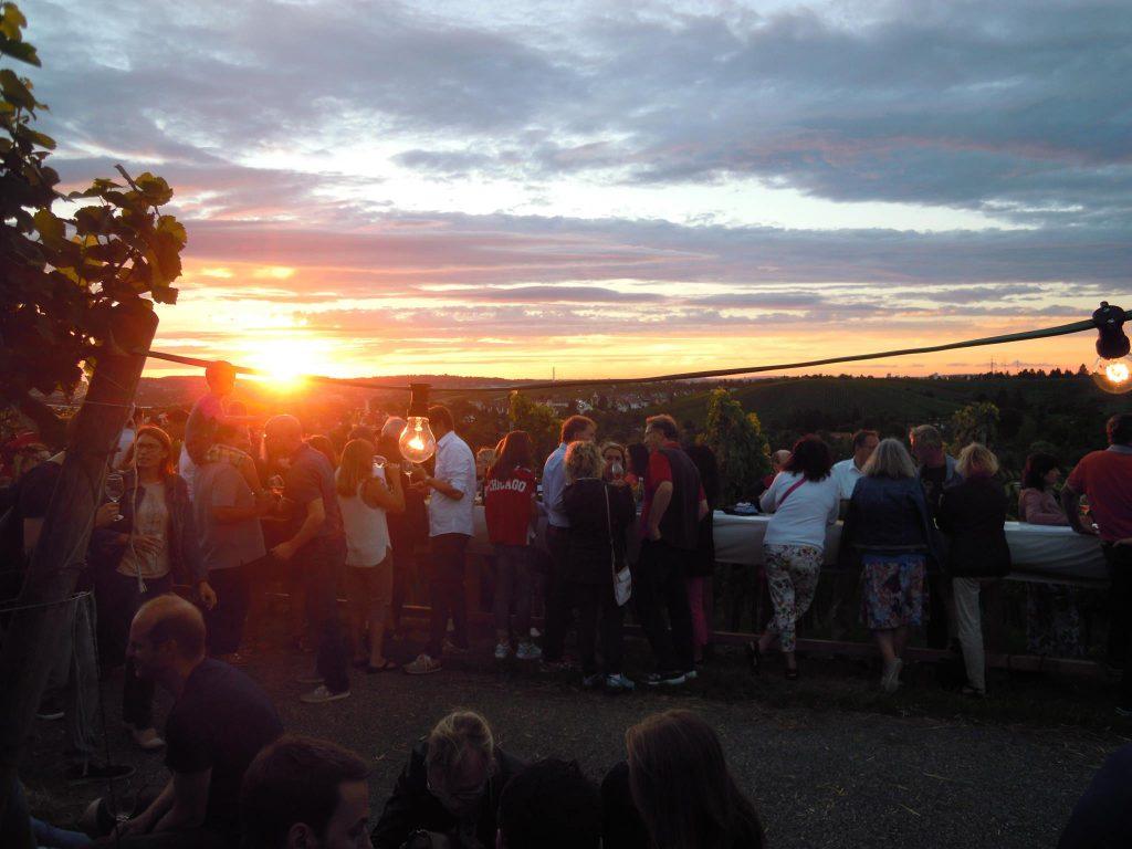 Man sieht Menschen beim feiern auf der Terrasse des Collegium Wirtemberg, in der Abenddämmerung.