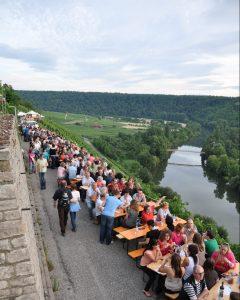 Man sieht zahlreiche Menschen an Biertischen in den Steillagen Hessigheims sitzen und sie Schräge WeinNacht feiern.