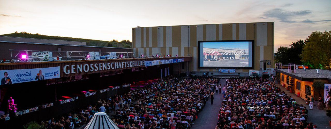Man sieht den Hof der Genossenschaftskellerei Heilbronn-Erlenbach-Weinsberg, gefüllt mit Menschen, die beim Open Air Kino Heilbronn einen Kinofilm ansehen.