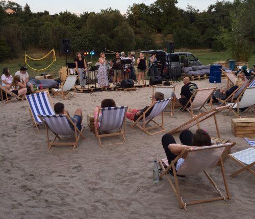 Man sieht Besucher des Weinstrandes am Heuchelberg in ihren Liegestühlen relaxen, im Hintergrund spielt eine Band.