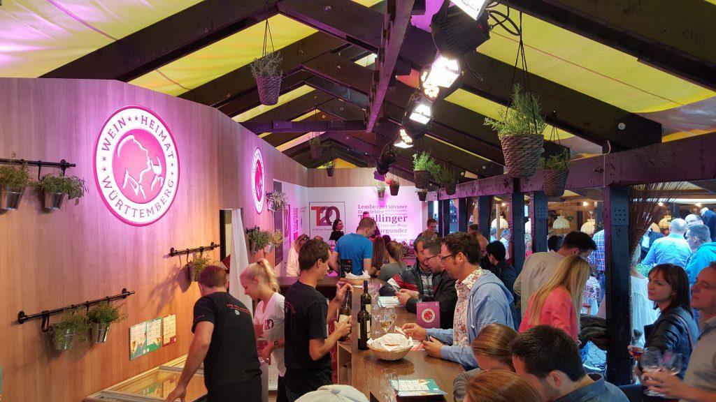 Man sieht die Theke der Württemberger Weingärtnergenossenschaften beim Stuttgarter Weindorf, es ist jede Menge los, einige Leute bestellen Wein.