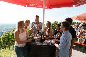 Gäste auf dem Weinfest stehen fröhlich um einen Fass-Tisch.