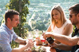 Bild von Personen, die Wein trinken. Im Hintergrund der Ausblick vom Wartberg.