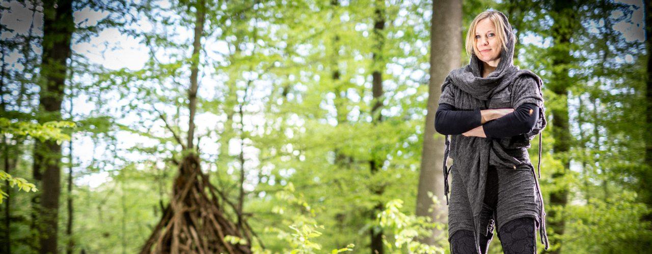 Thea Kornherr steht im Wald mit Kräutern