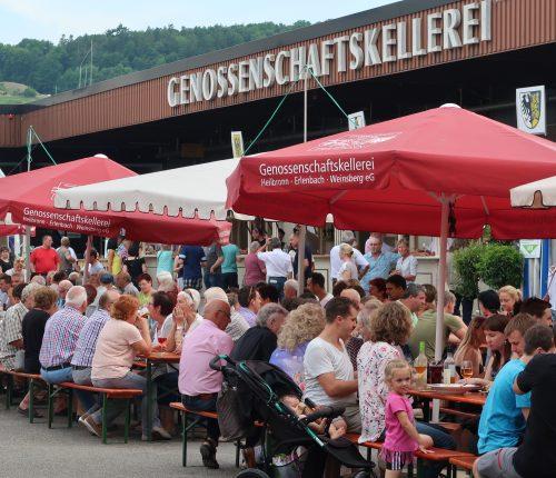 Menschen sitzen draußen an Tischen beim Heilbronner Sommerfest vor der Genossenschaftskellerei Heilbronn