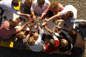 Menschen stoßen mit Wein an einem Tisch an