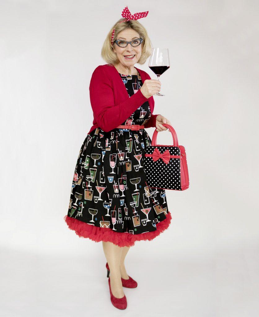 Elke Ott mit Weinglas für eine Bühnenshow