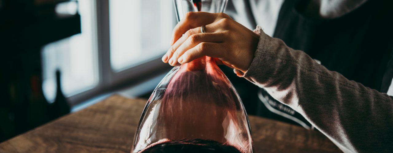 Spannende Fakten über Wein. Man sieht wie Wein in eine Karaffe geschenkt wird.
