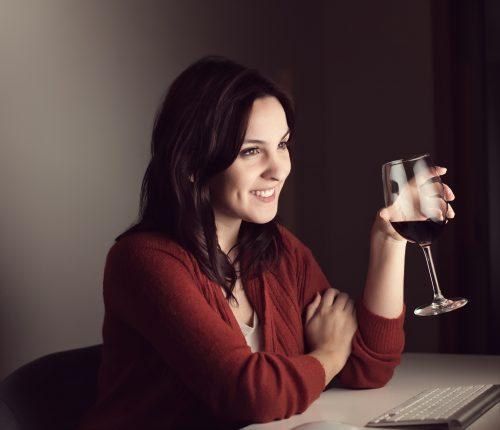 Online Weinprobe. Eine Frau trinkt Wein vor ihrem PC.
