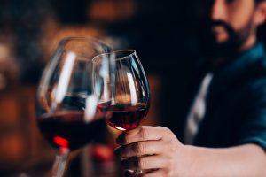 Zwei Personen stoßen mit Rotwein an.
