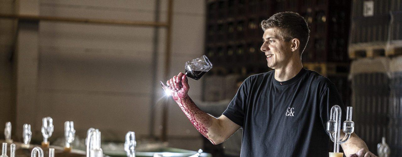 Lukas Ernst steht vor Weinfässern und probiert aus einem Rotweinglas. Roter Traubensaft läuft ihm über den Arm. Für ihn ist sein Beruf eine Lebenseinstellung.
