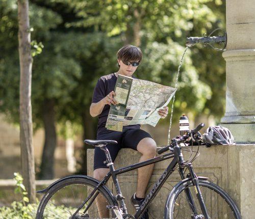 Ein Radfahrer auf dem Württemberger Weinradweg guckt sich eine analoge Karte an