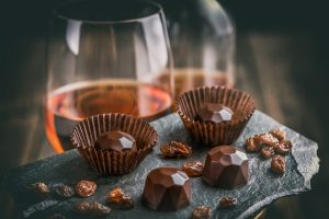 Weingläser mit Schokoladen Pralinen im Vordergrund