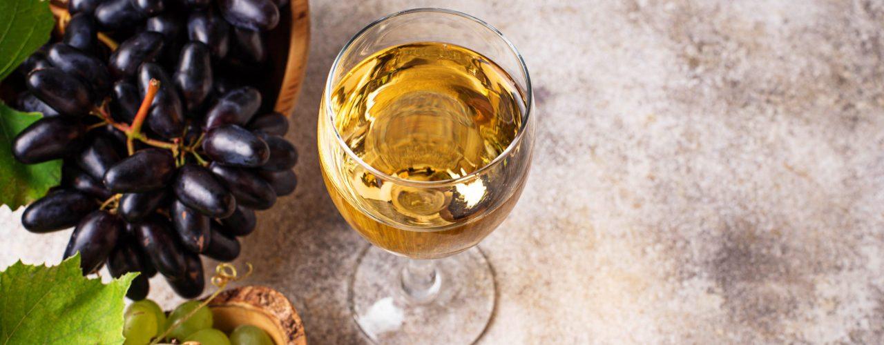 Irrtümer über Wein. Man sieht ein Glas Weißwein mit Trauben und einer Korkflasche