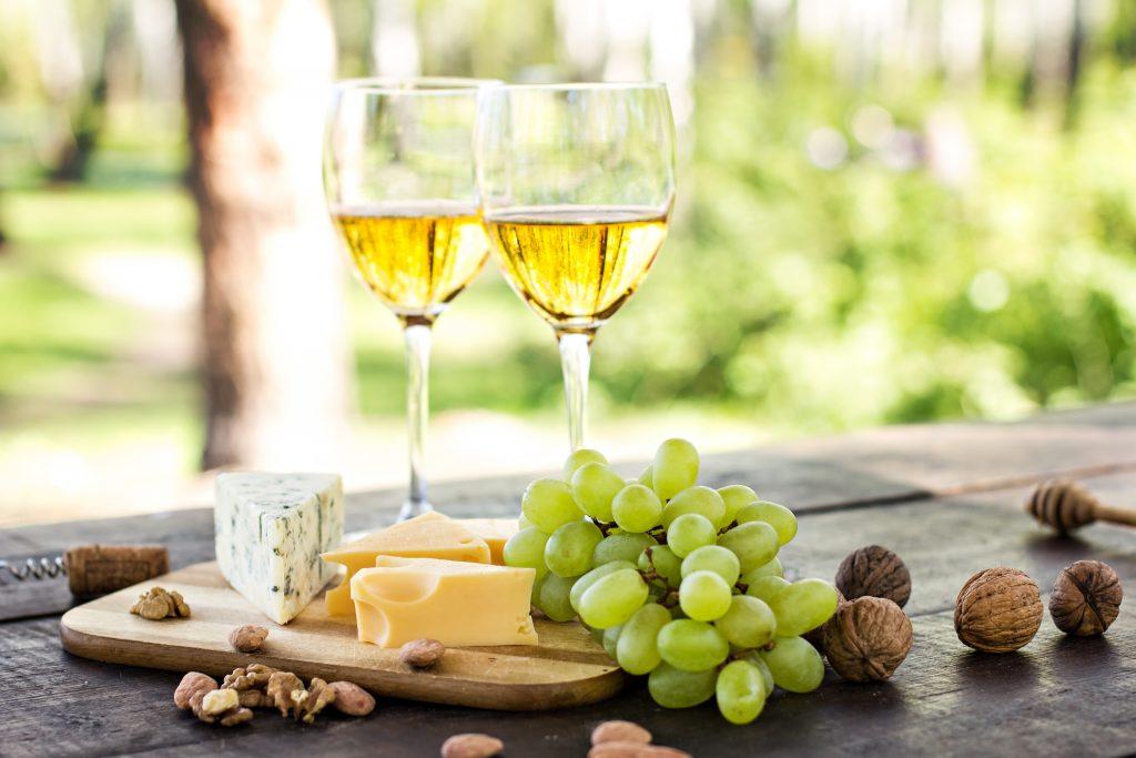 Irrtümer über Wein. Man sieht Weißweingläser mit Trauben und verschiedenen Käsesorten