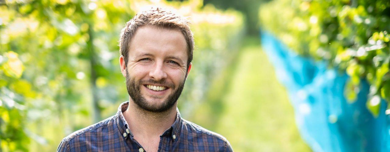 Patrick Hilligardt steht im Weinberg mit einer Traube in der Hand. Er ist einer von 16 German Wine Professional