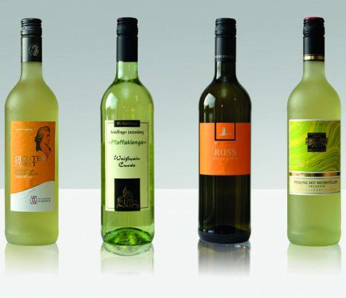 Verspielte Weißwein-Cuvées. Man sieht vier Flaschen Weißwein der Weinheimat Württemberg vor einem grauen Hintergrund.