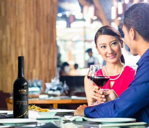 Asiatisches Paar am Stehtisch, das mit Rotwein anstößt