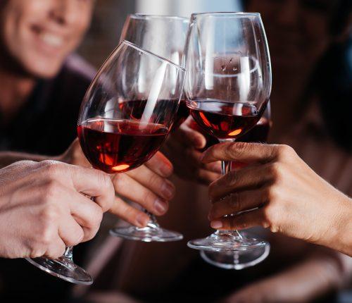 Live Verkostungen zum Sommeranfang | Man sieht vier Personen die mit Rotwein anstoßen.
