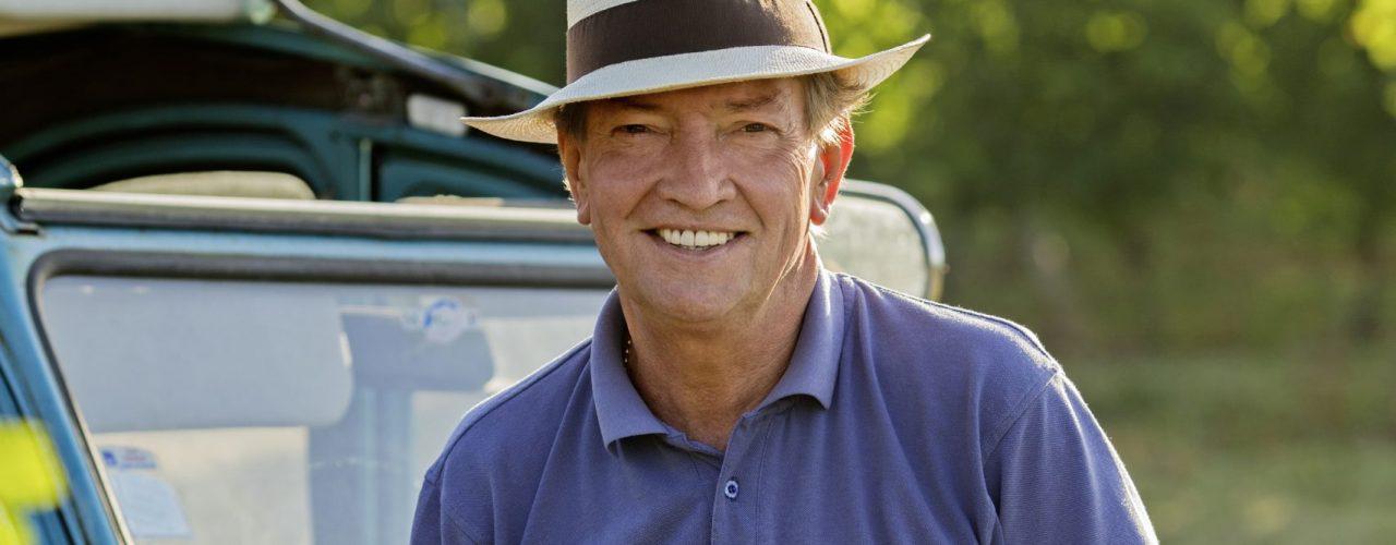 Portrait von Martin Walker vor seinem Auto mit einem Hut auf dem Kopf und einem Glas Rotwein in der Hand