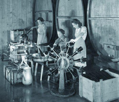 Arbeiterinnen stehen vor großen Fässern