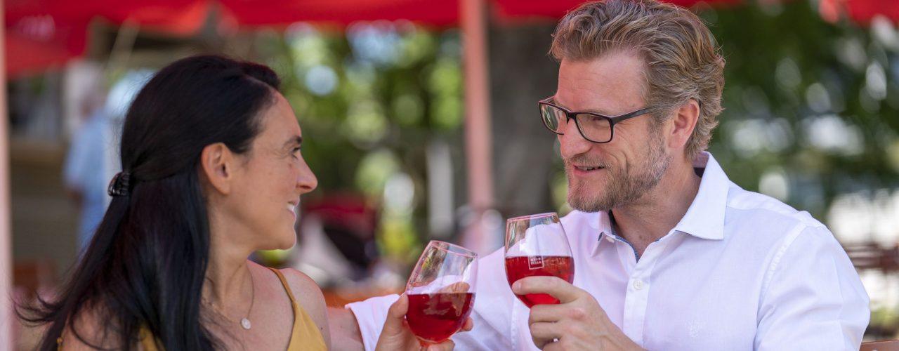 Ein Paar sitzt im Weinpavillon an der Neckarbühne und genießt ein Glas Wein