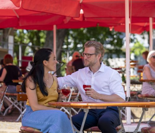 Ein Paar sitzt im Weinpavillon an der Neckarbühne unter einem Sonnenschirm und genießt ein Glas Wein