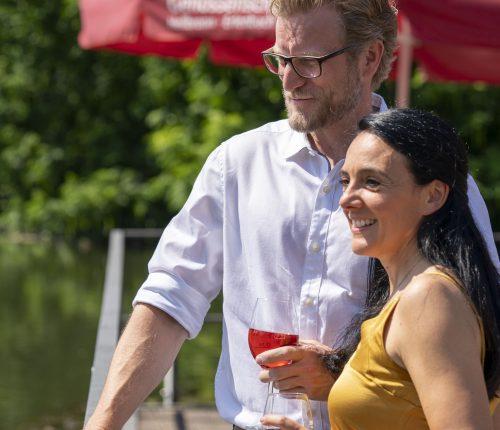 Ein Paar steht am Neckar und genießt ein Glas Wein