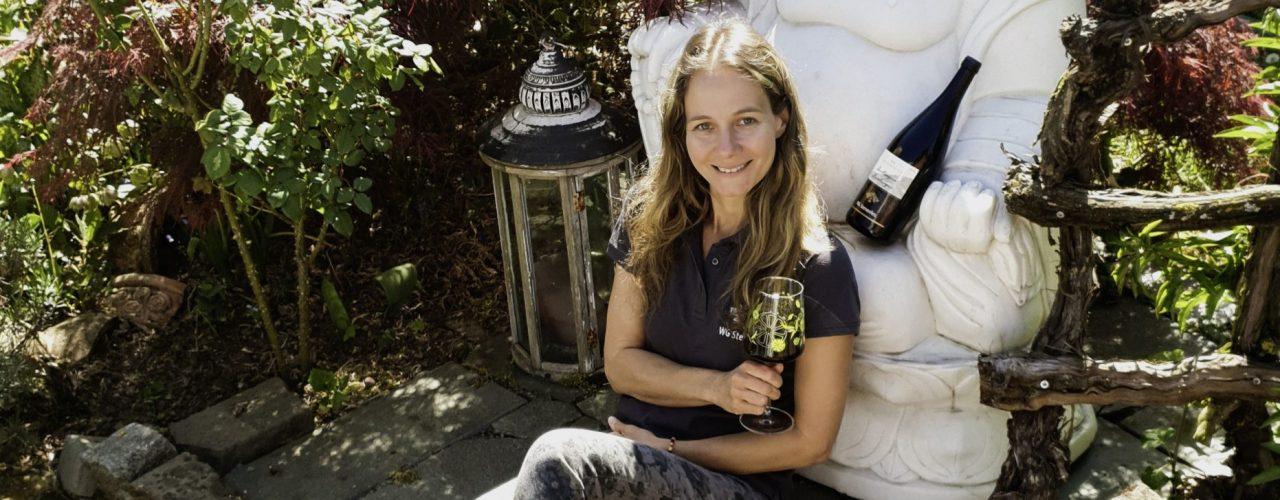 Britta Kunkel posiert mit einem Glas Wein im Grünen