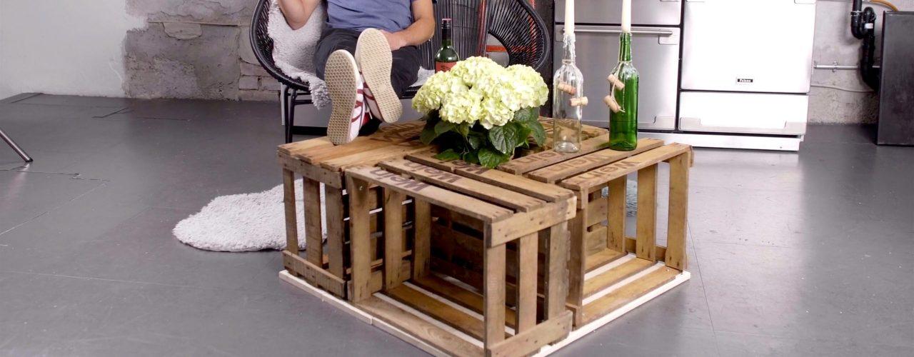 Weinkisten-Tisch DIY, man sieht einen Mann mit Weinglas auf einem Stuhl sitzen. Die Beine auf einen selbstgebauten Weinkisten Tisch gelegt