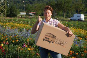 """Petra Rapp von den Weingärtner Esslingen posiert mit einem Karton von """"Lecker aufs Land"""""""