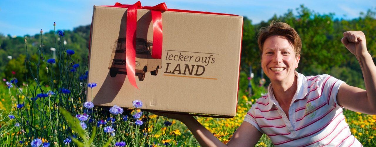 """Petra Rapp vor einem Blumenfeld mit der """"Lecker aufs Land"""" Überraschungskiste"""