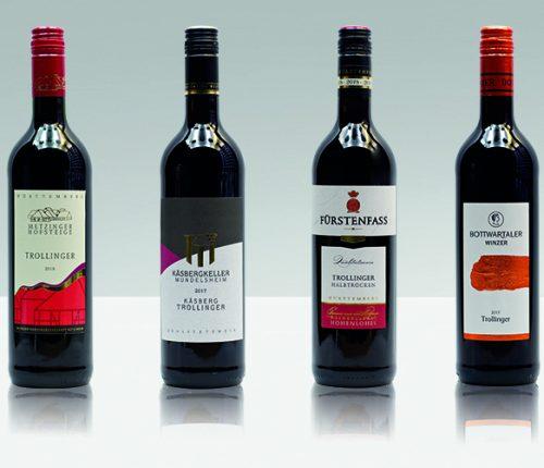 Vier Flaschen Trollinger halbtrocken vor grauem Hintergrund