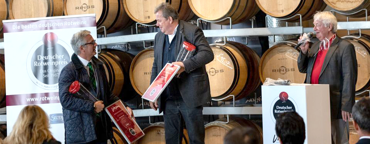 Man sieht Mirko Semmler-Lins (Geschäftsführer Weinkonvent Dürrenzimmern) und Kurt Freudenthaler (Kellermeister Weinkonvent Dürrenzimern) bei der Übergabe ihrer Auszeichnung durch Moderator Rudi Knoll vom vinum Magazin