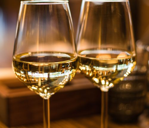 Live-Tastings im November. Man sieht zwei gefüllte Weingläser in warmem Licht.