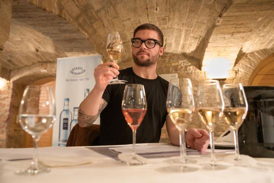 Mann schaut prüfend auf einen Weißwein im Glas