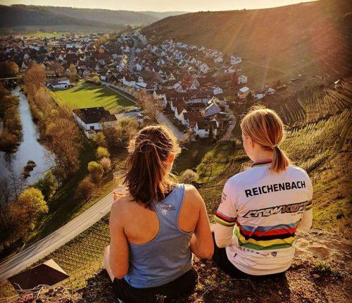 Man sieht zwei junge Frauen von hinten, sitzend oberhalb der Rosswager Halde, mit Blick auf Rosswag.