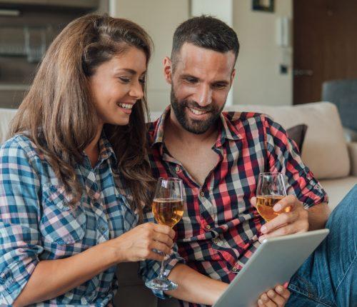 Online Verkostungen im Mai. Pärchen sitzt mit Weingläsern auf dem Sofa und schaut in ein Tablet.