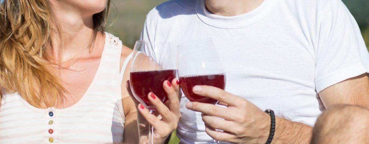 Pärchen das Wein trinkt und anstößt