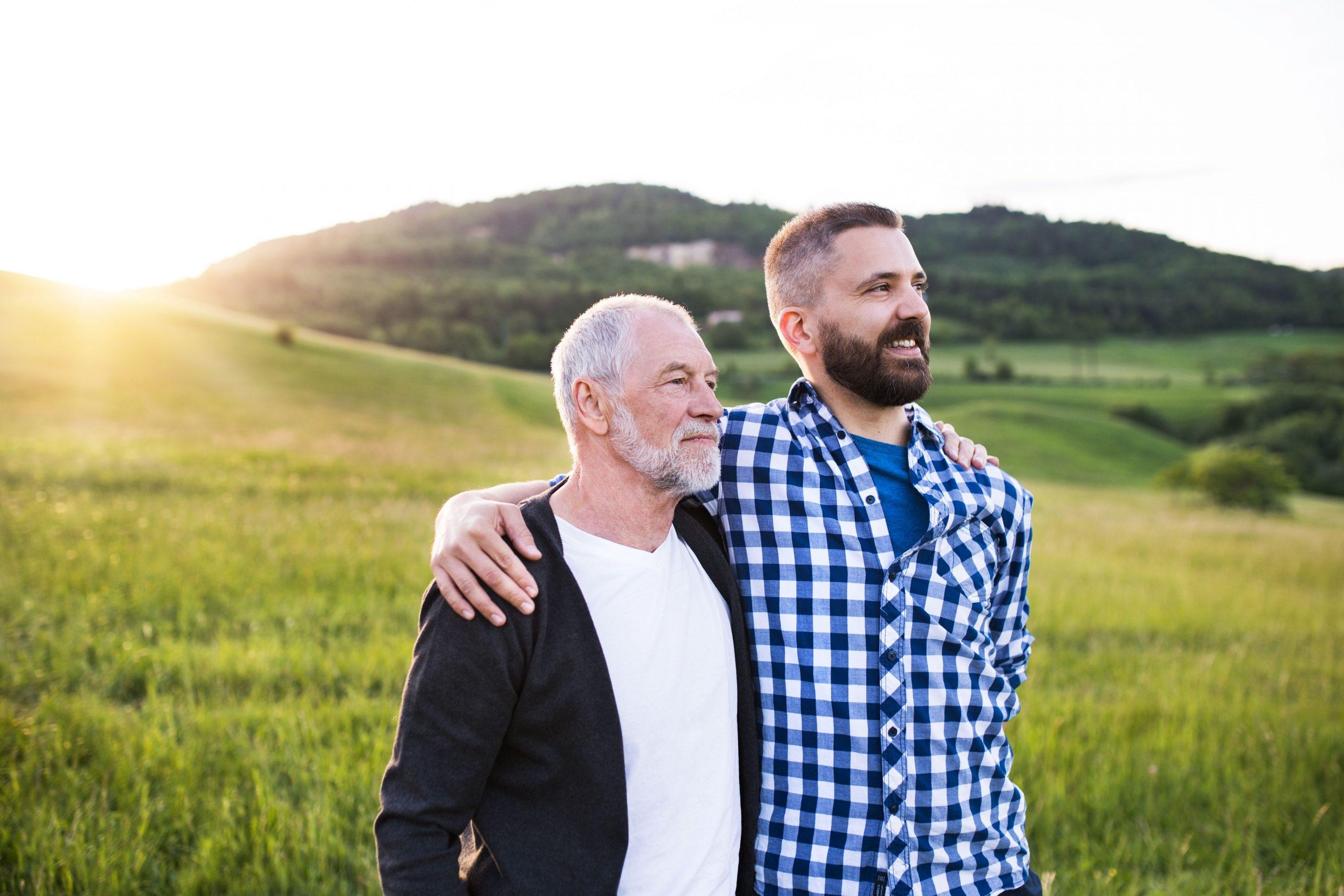 Vater steht mit seinem erwachsenem Sohn auf einer grünen Wiese