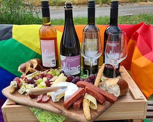 Vesperbrett und die vier Weine der Fellbacher Weingärtner, mit denen der CSD 2021 in Stuttgart unterstützt werden soll, vor einer Regenbogenflagge