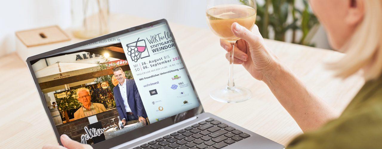 Frau sitzt mit einem Glas Wein vor dem Computer und schaut sich das Stuttgarter Weindorf online an