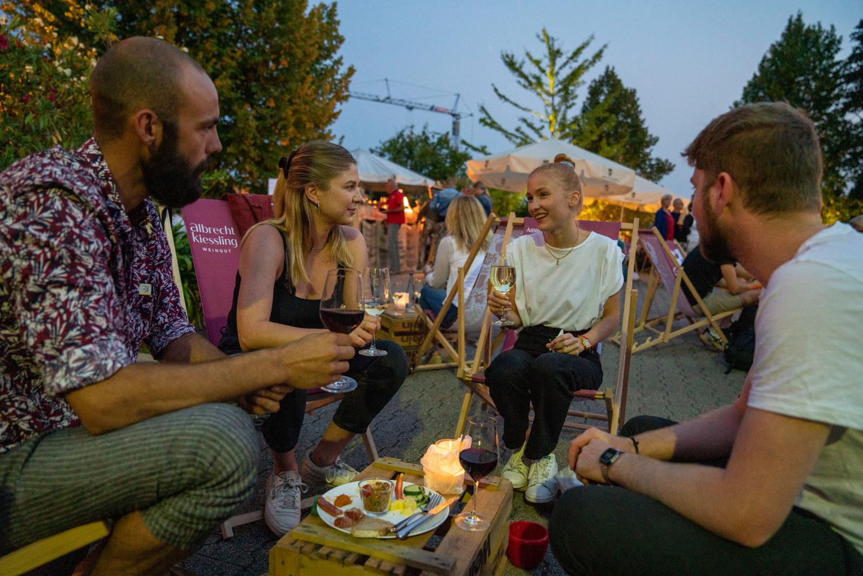 Heilbronner Weindorf Auslese: Man sieht Besucher einer Veranstaltung auf einem Weingut gemütlich zusammensitzen
