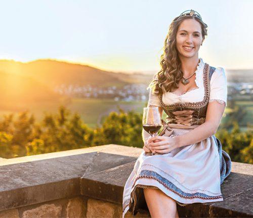 Weinprinzessin Henrike Heinicke: sitzt mit einem Weinglas im Dirndl auf einer Mauer.